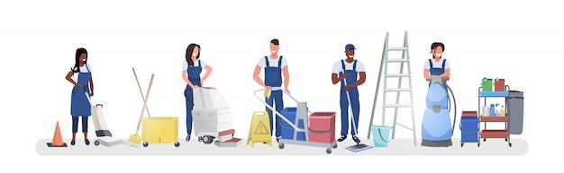 Смешанные расы дворники, стоящие с уборочным оборудованием, улыбаясь команда уборщиков в униформе, работая вместе, концепция уборки горизонтальная полная длина