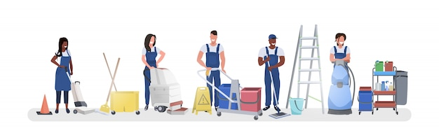 Mix race janitors standing with cleaning equipment smiling cleaners team in uniform working together cleaning service concept horizontal full length