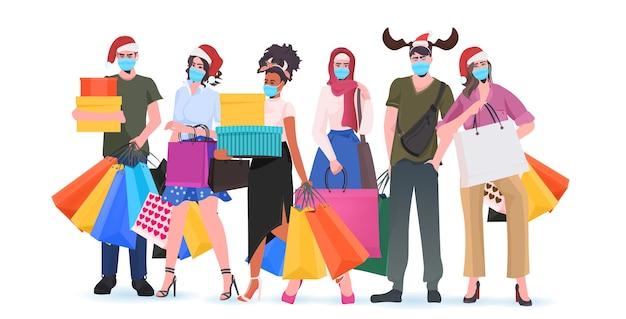 コロナウイルスを防ぐために、買い物袋を持ったお祝いの帽子をかぶった混血男性女性マスクを着用