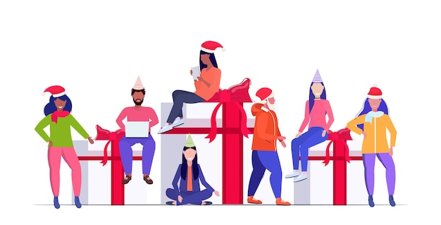 Mix race people in santa hats preparing for christmas and new year party celebration men women sitting on gift present boxes winter holidays