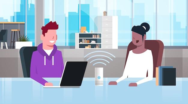 음성 인식 인공 지능 지원 현대 사무실 인테리어와 지능형 스마트 스피커를 사용하여 직장 책상 남자 여자에 앉아 혼합 인종 사람들