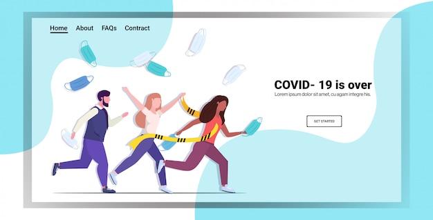 黄色のテープに沿って走るフェイスマスクを投げる人種混合の人々コロナウイルスのパンデミック検疫の終了
