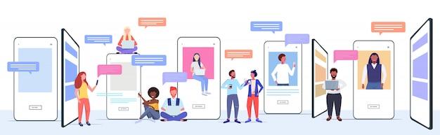 デジタルデバイスのチャットアプリを使用してレースの人々をミックスソーシャルネットワークチャットバブル通信の概念