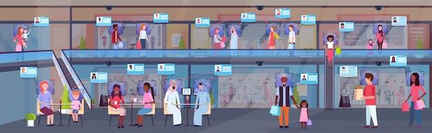 Смешанные расы люди ходьба современный большой торговый центр распознавание лиц концепция безопасности камера видеонаблюдения система видеонаблюдения супермаркет интерьер горизонтальный полная длина плоский