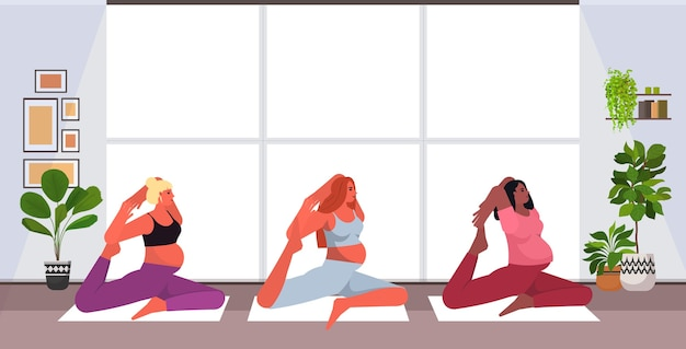 Mix race pregnant women doing yoga fitness exercises training healthy lifestyle concept girls meditating together modern studio interior