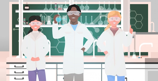 Mix race pupils in uniform holding test tubes working in chemical laboratory modern science classroom interior horizontal portrait