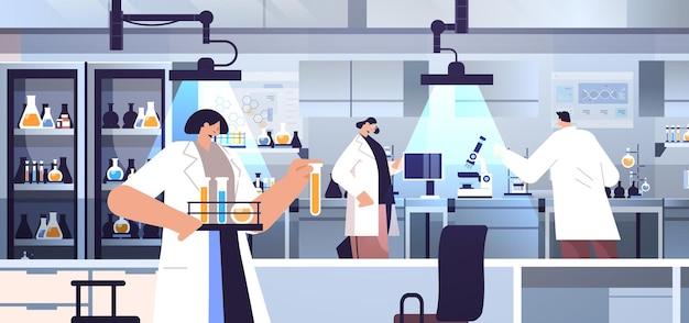 実験室で化学実験を行う試験管研究者と協力する混血研究科学者チーム