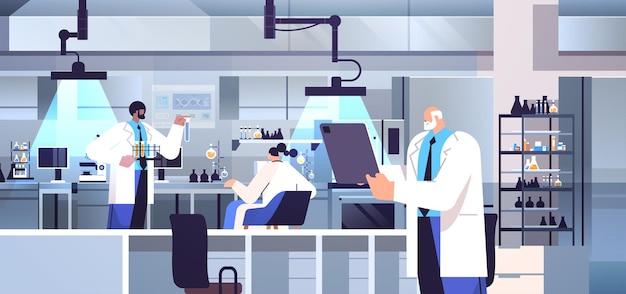 Группа ученых-исследователей смешанной расы, работающая с исследователями пробирок, проводящими химические эксперименты в лаборатории