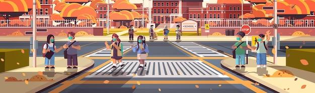 Mix race schoolchildren in masks crossing road on crosswalk pupils walking to school coronavirus pandemic