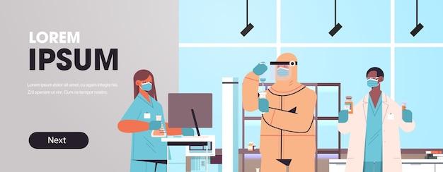 医療ラボワクチン開発コンセプトで働くコロナウイルス研究者チームと戦うためにワクチンを開発している混血科学者コピースペース水平バナー