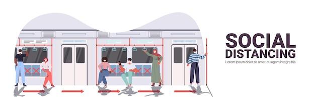Смешанная гонка пассажиры метро в защитных масках, соблюдающие дистанцию для предотвращения коронавируса в общественном транспорте, концепция социального дистанцирования, интерьер поезда метро, копировальное пространство