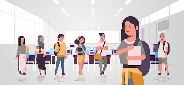 Ключевые слова на русском: смешанные расы подростковой группа студентов с рюкзаками, держа книги, стоя вместе образования концепция современного университета классная комната плоский горизонтальный