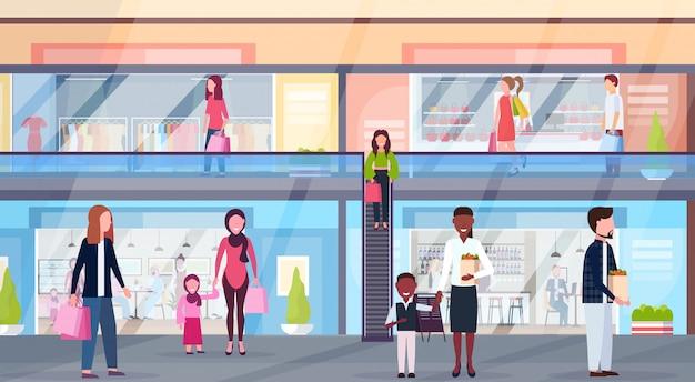 Посетители смешанной расы, идущие в современный торговый центр с бутиками одежды и кафе, супермаркет, розничный магазин, интерьер, горизонтальный, полная длина