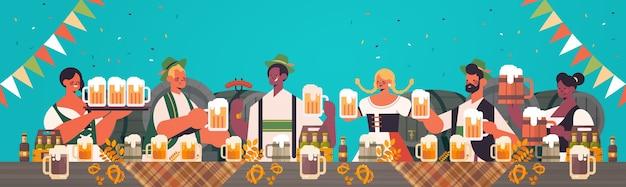 Официанты смешанной расы с пивными кружками концепция празднования вечеринки на октоберфесте люди в традиционной немецкой одежде веселятся
