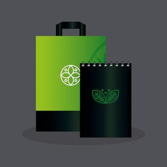 Мокап блокнота и бумажная сумка зеленого цвета со знаковыми листьями, зеленый фирменный стиль