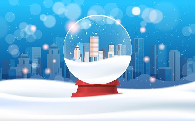 魔法のガラス玉の近代的な都市の建物の高層ビルメリークリスマス新年あけましておめでとうございます冬の休日のお祝いのコンセプト降雪街並み