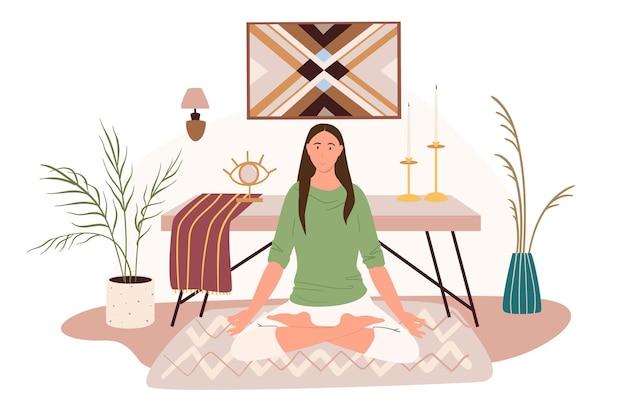 요가 웹 개념에 대한 현대적인 편안한 인테리어. 여자는 테이블, 양초, 장식, 식물과 함께 방에 카펫에 앉아 명상