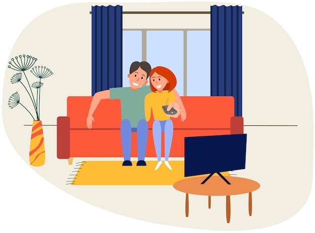 ソファの上のリビングルームでテレビを見ている現代のカップル