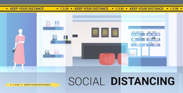 社会的な距離を置く黄色いステッカーコロナウイルスの流行保護対策の兆候を備えたモダンなファッションブティック