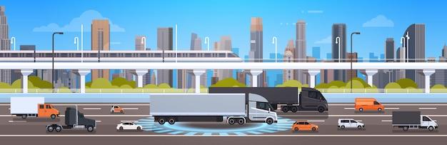 都市の背景の上の車、大型トラックおよび貨物トラックが付いている現代高速道路