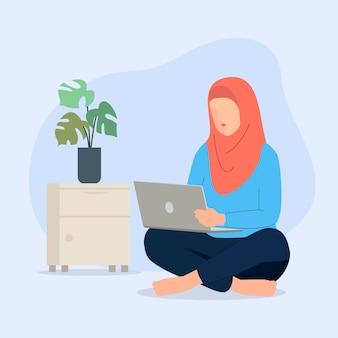 Мусульманские женщины с ноутбуком, сидя на полу.