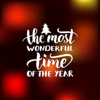 The most wonderful time of the year lettering design on blurred background. christmas or new year typography for greeting card template or poster concept.