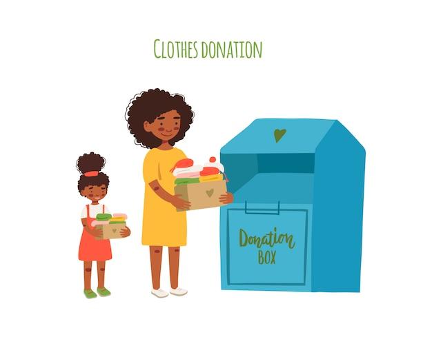 기부금에 대 한 의류와 골 판지 상자를 들고 어머니와 딸