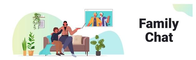 母と息子のビデオ通話中にwebブラウザーウィンドウで祖父母との仮想会議を持つ家族のチャットコミュニケーションコンセプトリビングルームインテリア水平