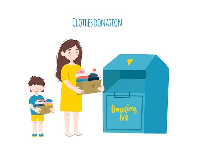 寄付やリサイクル用の衣類と衣類用の容器を入れた段ボール箱を持つ母と息子。
