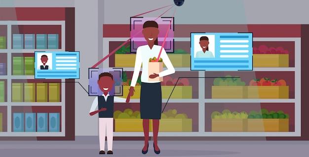 Мать и сын держат покупки бумажный пакет с продуктами клиенты идентификации лица концепция распознавания камеры видеонаблюдения система видеонаблюдения система продуктовый магазин интерьер полная длина горизонтальный
