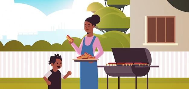 어머니와 아들 그릴에 핫도그를 준비 행복 한 흑인 가족 재미 뒤뜰 피크닉 바베큐 파티 개념 평면 초상화 가로