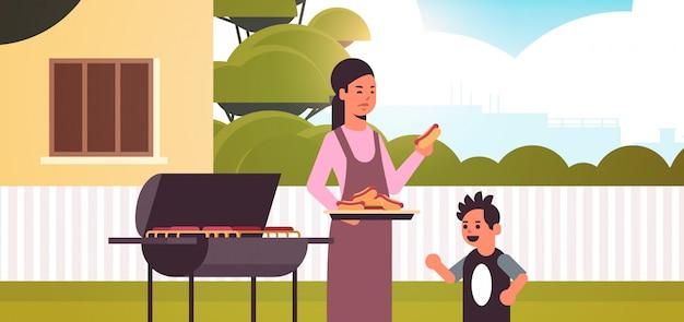 母と息子のグリルでホットドッグを準備する幸せな家族楽しんで裏庭ピクニックバーベキューパーティーコンセプトフラット縦肖像画