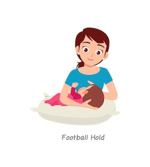 サッカーホールドという名前のポーズで母乳育児の赤ちゃん