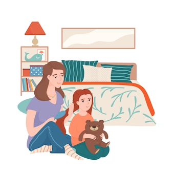 Mother combing hair of her little daughter with a brush, both sitting on the floor in bedroom with bed, shelf stand, lamp and picture on the wall, happy motherhood