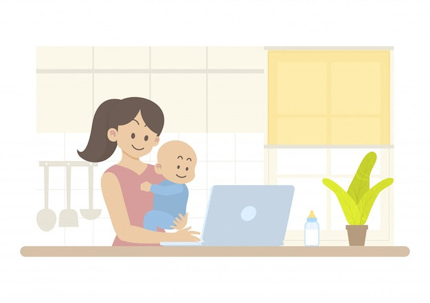 어머니는 행복한 아기를 들고 부엌에서 랩톱 컴퓨터에서 작동