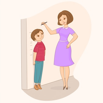 Mother measuring her son's height at the wall