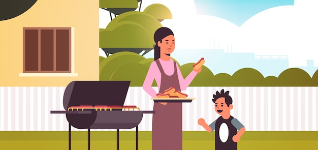 Mother and son preparing hot dogs on grill happy family having fun backyard picnic barbecue party concept flat portrait horizontal