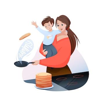 息子とおいしいパンケーキを調理し、男の子の子供を手に持って、幸せな母性と母の時間