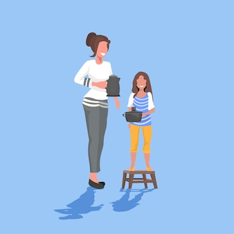 Mother with daughter holding kettle doing housework together