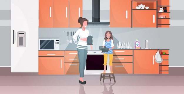 Mother with daughter holding kettle doing housework