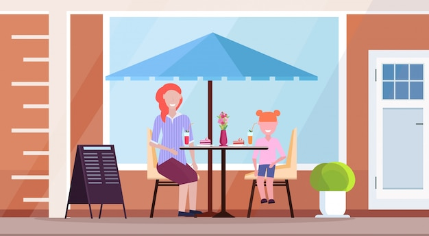 Mother with daughter sitting modern summer cafe drinking cocktails and eating cakes street restaurant terrace outdoor cafeteria exterior flat horizontal full length