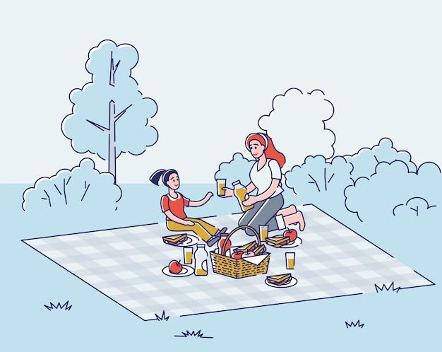 담요에 앉아 딸과 함께 어머니는 휴가 또는 주말에 신선한 공기 속에서 함께 시간을 보냅니다.