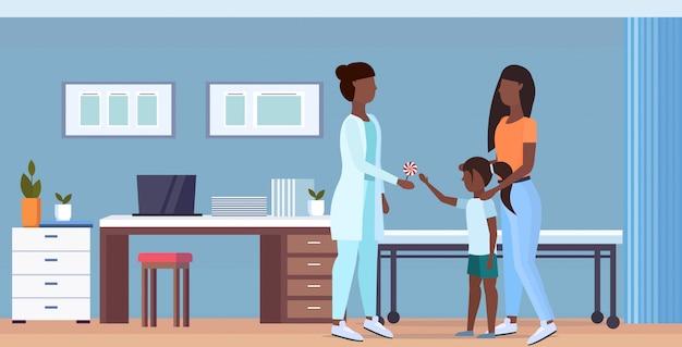 小さな女の子相談ヘルスケアコンセプト現代病院インテリア全長水平にロリポップを与える医者小児科医を訪れる娘を持つ母