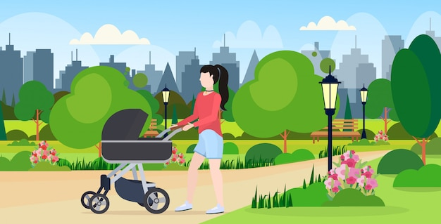 Mother with her baby in stroller walking outdoor woman pushing pram with newborn child happy family motherhood concept urban city park landscape background  full length horizontal
