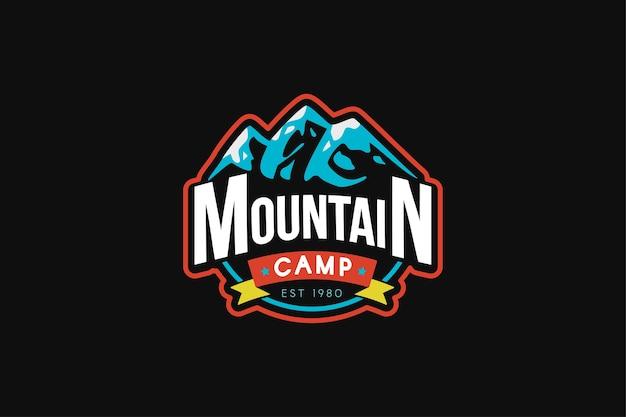 マウンテンキャンプのロゴテンプレート。タイポグラフィと岩のイラスト。登山レトロバッジ