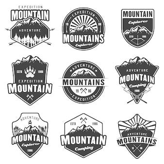 山の旅、アウトドアアドベンチャー、キャンプ、ハイキングの黒のエンブレム、ラベル、バッジ、白い背景のロゴのセット