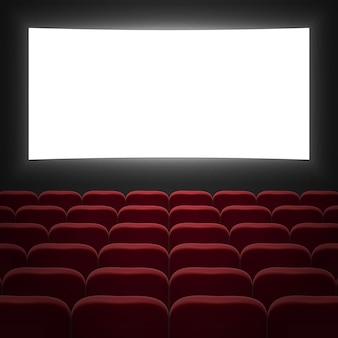 白いスクリーンと赤い列の椅子のある映画館