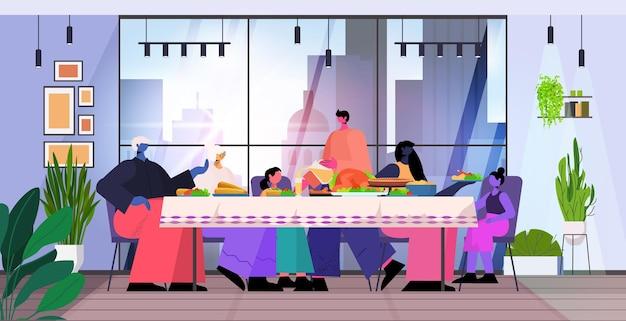 전통적인 저녁 식사를 하는 테이블에 앉아 행복한 추수 감사절을 축하하는 다세대 가족