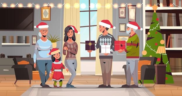 Семья из нескольких поколений в шляпах санта-клауса держит подарочные коробки празднует счастливого рождества с новым годом зимние каникулы концепция современный интерьер гостиной