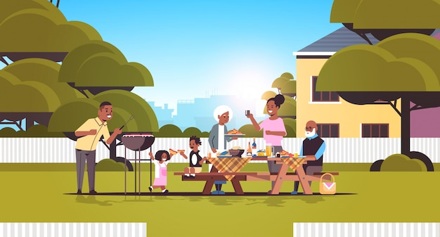 Multi generation family preparing hot dogs on grill african american grandparents parents and children having fun backyard picnic barbecue party concept flat full length horizontal